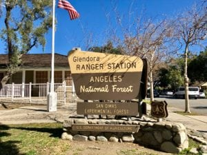 Glendora Ranger Station sign with Ranger station and American Flag in background
