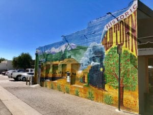 Beautiful mural of train and orange trees on side of building representing Historic Old Town La Verne