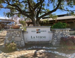 Sign displaying Old Town La Verne in front of large oak tree and Warehouse Pizza company